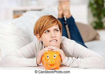 Woman With Piggy Bank While Lying On Sofa - Portrait of...