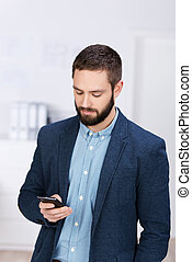 Businessman Text Messaging Through Cell Phone - Young...