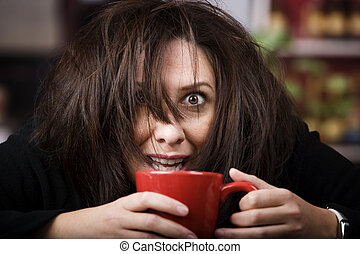 Coffee-Crazed Woman - Half awake woman cradling a mug of...