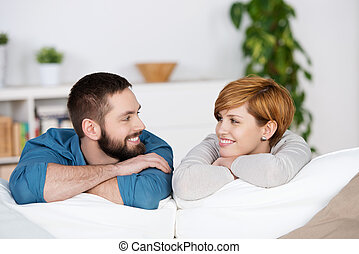 Couple Looking At Each Other On Sofa - Happy young couple...