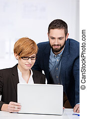 Smiling business man and woman in a meeting using laptop