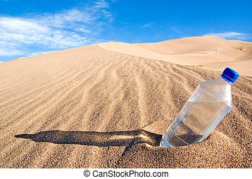 thirst - A cold bottle of water sitting in a sand dune