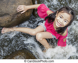 Asian girl sitting near the waterfall