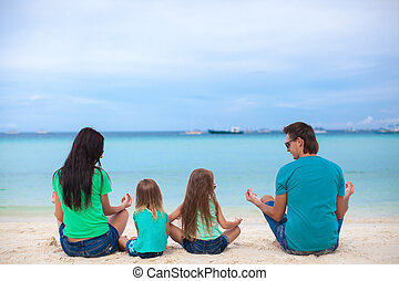 Rear view of a family of four sitting in the lotus position...
