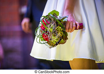 bride holds wedding bouquet - brides hand holds a green...