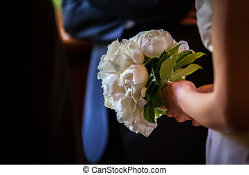 white bridal bouquet - brides hand holding a beatiful...