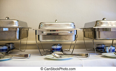 silver chafing-dishes - three silver chafing-dishes on a...