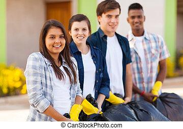 teenage volunteers standing with waste bags - happy teenage...