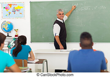 middle aged teacher teaching mathematics - cheerful middle...