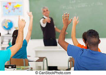 high school students with hands up in classroom - group of...