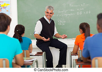 male teacher explaining lesson to students
