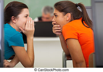 cute high school students gossiping in classroom