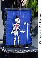 Skeleton puppeteer singing in the street