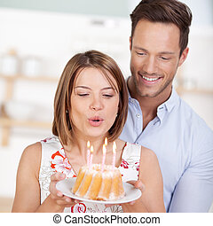 Blowing candle cake - Happy woman blowing a candle on cake...
