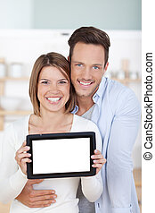 Tablet computer - Smiling young couple holding tablet...