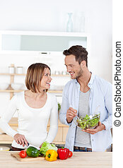 Man and woman in their Kitchen at home preparing vegetable...