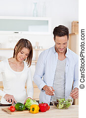 Healthy eating with a young couple preparing salad in the...