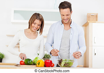 Couple preparing salad in the kitchen - Attractive young...
