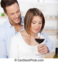Smelling red wine - Young attractive couple smelling a red...