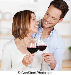 Red wine - Young romantic couple cheers with red wine in a...