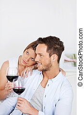 Drinking red wine - In love couple sitting on sofa and...