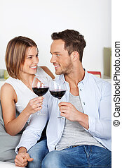 Cheers with red wine - Smiling couple dating and drinking...