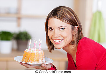 Beautiful woman holds a birthday cake with candles -...