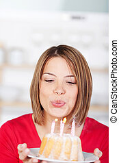 Woman blowing out her birthday candles holding a small...