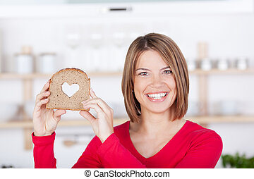 Smiling woman holding a bread with a hearth shape - Smiling...