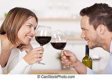 Happy couple toasting with red wine leaning towards each...