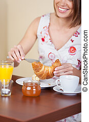 Young woman having breakfast in a cafe enjoying a fresh...