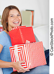 Smiling woman with a pile of gifts