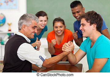 middle aged teacher arm wrestling with high school student