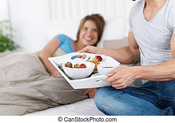 Breakfast in bed - Man delivering breakfast on the tray to...