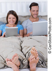 Couple in bed with laptop