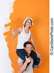 Man carries his girlfriend on his shoulders, while painting