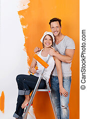 Happy couple redecorating and painting with orange color