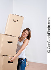 Woman carrying a stack of cardboard cartons as she packs up...