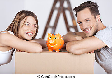 Couple and piggybank - Conceptual portrait of new couple...