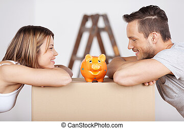 Couple with piggybank - New happy couple looking at the...