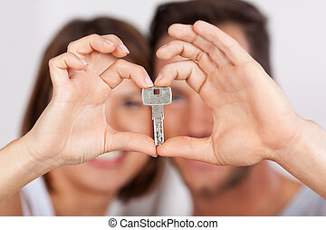 Young couple holding a house key together with their hands...