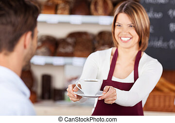 Bread store - Bakery shopkeeper gives coffee to customer at...