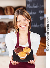 Female bakery worker with fresh muffins holding them out on...