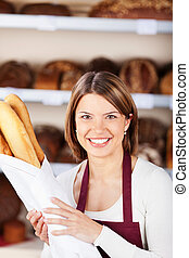 Happy bakery worker with baguettes - Happy bakery worker...