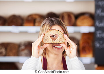 Smiling woman looking through a bread with heart hole
