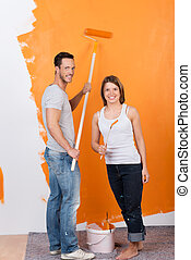 Young adult couple - A young adult couple painting yellow...