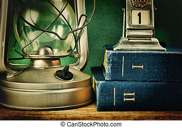 old kerosene lamp and a stack of books