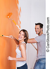 Home decorating - Young couple having fun while painting the...