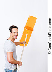 Young man painting a white wall orange