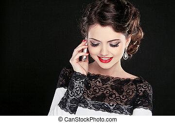 Young happy woman talking on mobile phone. Fashion Brunette Model Portrait. Jewelry. Make Up. Red Lips.